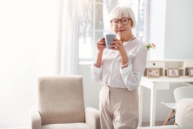 Любитель кофе. довольно старшая женщина в стильном наряде позирует, держа чашку кофе, наслаждаясь его ароматом