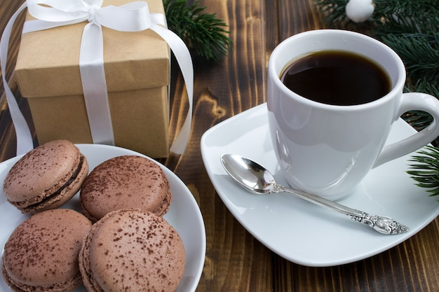 Coffee, macaroons and christmas gift on the wooden background