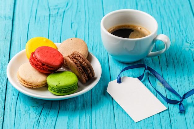 Coffee, macaroons and empty card on blue wooden table