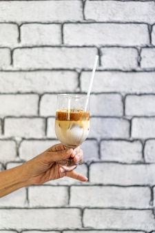 Coffee macchiato and milk layer with ice in champagne glass was held by asian grandmother hand in front of white brick wall wallpaper.