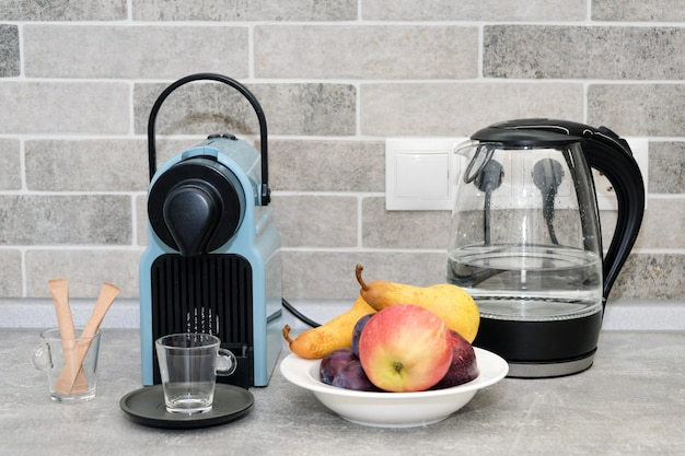コーヒーマシン、キッチンの電気ポット。白い皿に新鮮な果物。
