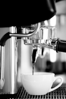 Кофеварка и белая керамическая чашка