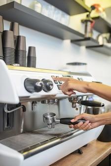 Кофеварка, бариста. женские профессиональные руки с держателем фильтра возле панели управления кофеваркой, без лица