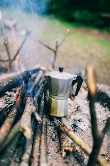 Coffee machine on fire in the mountains the atmosphere of the forest and aromatic coffee on a fire