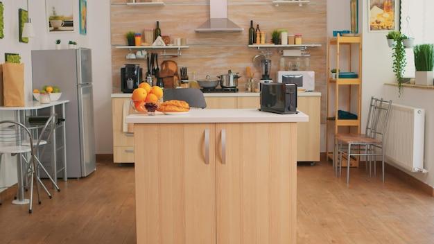 Кофеварка на кухне, в которой никого нет. современная столовая с кофеваркой в уютном интерьере с техникой и мебелью, отделкой и архитектурой, уютная комната.