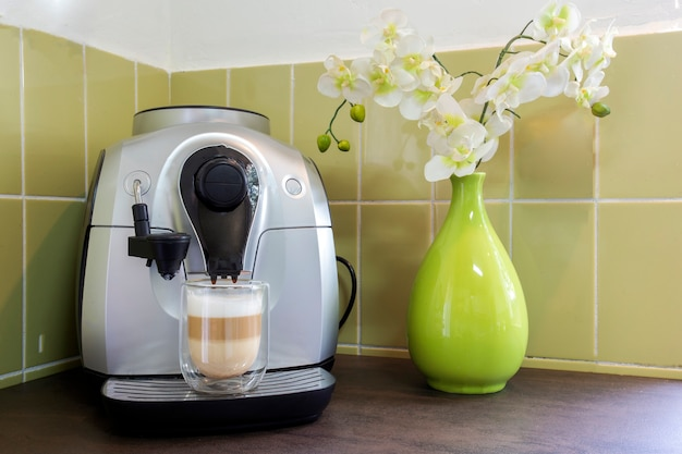 緑の壁と花のある居心地の良い装飾的な家にラテマキアートを置いたコーヒーメーカー。自家製コーヒー