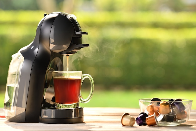 Coffee machine making coffee with capsules on wooden table