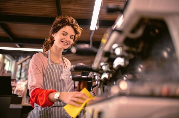 コーヒーメーカー。下を見ながら職場に立って喜んでいる女性