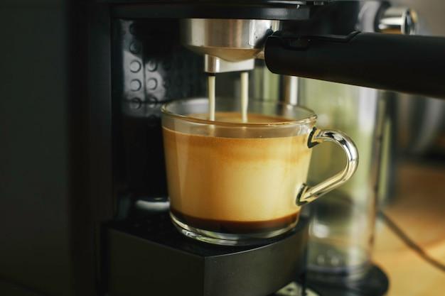 Coffee machine pours coffee into a transparent glass