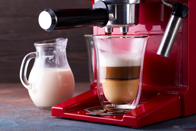 Coffee machine preparing fresh latte coffee and pouring into glass at restaurant, close up