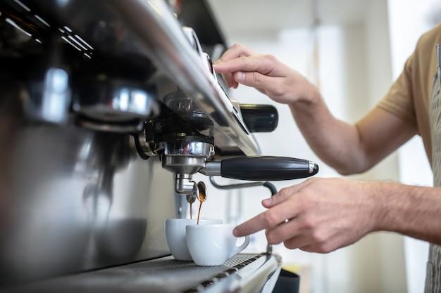 Запуск кофеварки. мужские руки возле кофемашины, нажимая старт, ждут, чтобы налить кофе в чашку, без лица