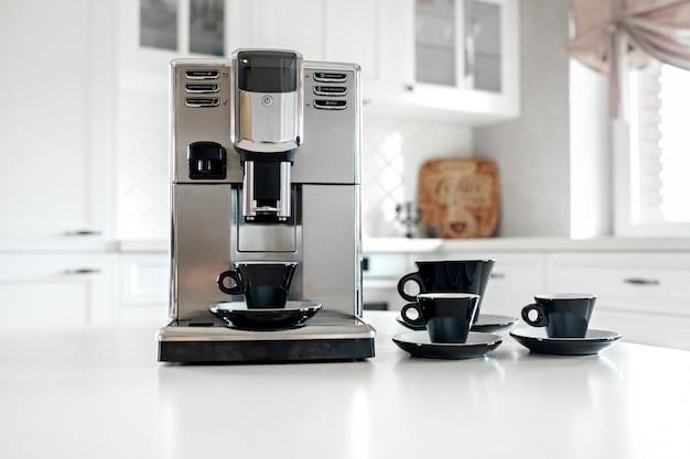 Coffee machine with cups for espresso on the kitchen table. close-up