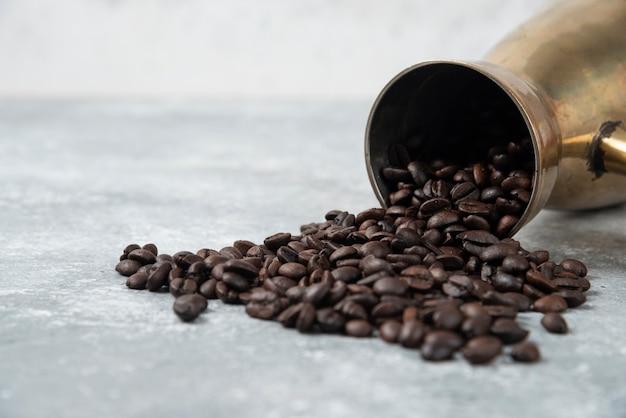 Кофеварка, полная жареных кофейных зерен на мраморной поверхности.