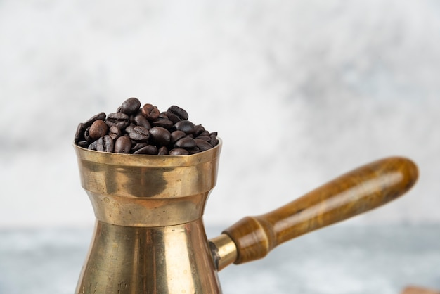Caffettiera piena di chicchi di caffè tostati sulla superficie in marmo.