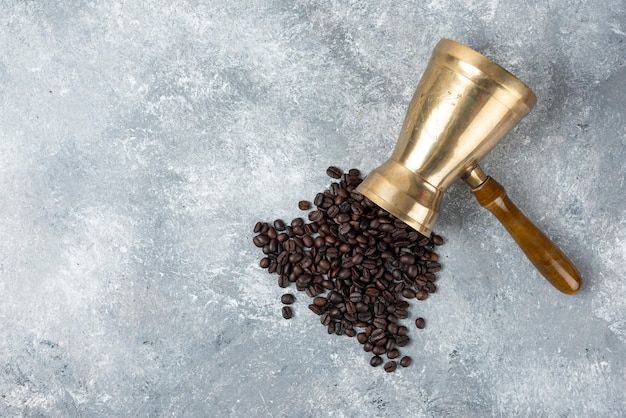 Coffee maker full of roasted coffee beans on marble surface.