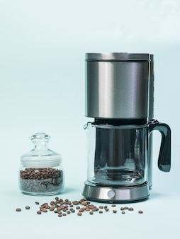 Coffee maker and glass jar with coffee beans on a blue background. the concept of a classic breakfast.