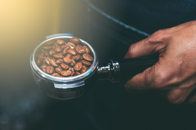 The coffee maker holds a device that contains coffee beans.
