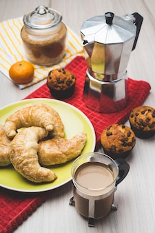 Coffee maker, muffins, croissant, tangerine and cup of coffee