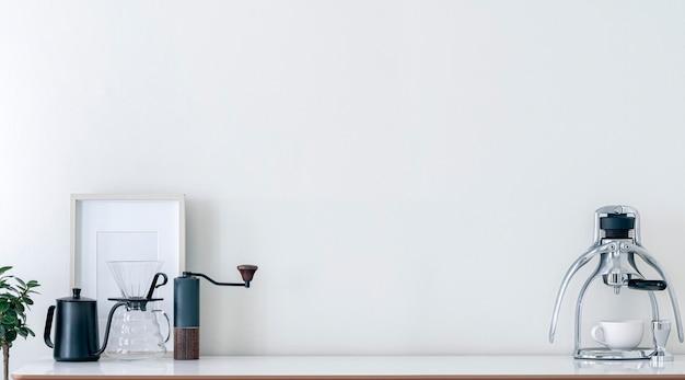 Оборудование для приготовления кофе украшает белый стол с копией пространства и панорамным видом. мокап для приготовления кофе на деревянном столе с копией пространства.