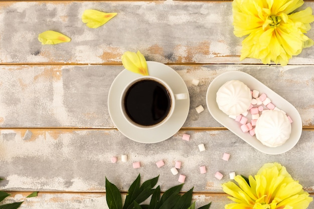 Coffee and marshmallows on wooden background composition with flowers.