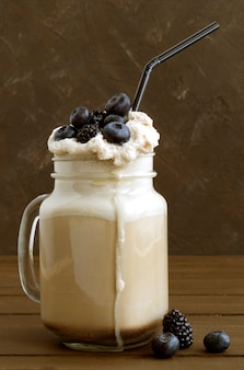 Coffee milk shake with fresh berries on wooden background.
