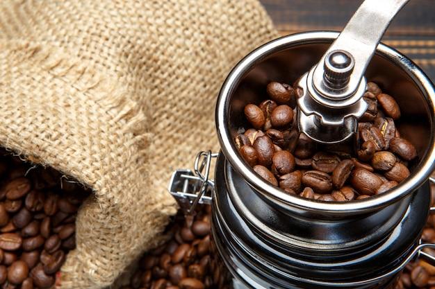 コーヒーミルと木製の背景にロースト豆