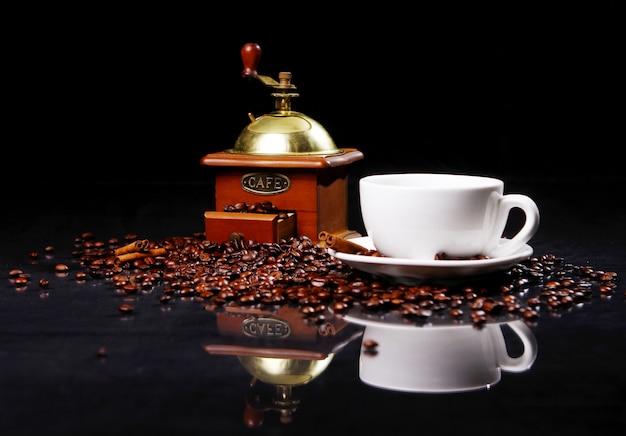 Кофемолка на столе с кофейными зернами вокруг