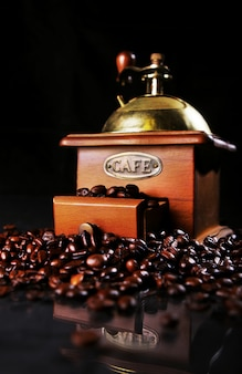 Coffee mill on the table with coffee beans around