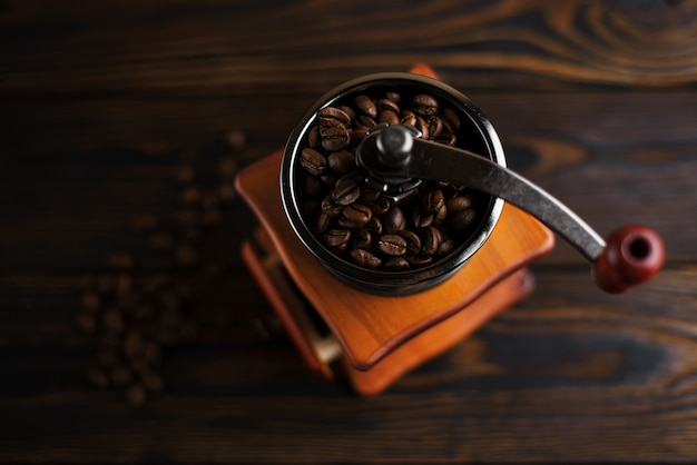 Coffee mill on a wooden table in a rustic style. coffee beans in a manual coffee mill on a rustic table with a dark color.