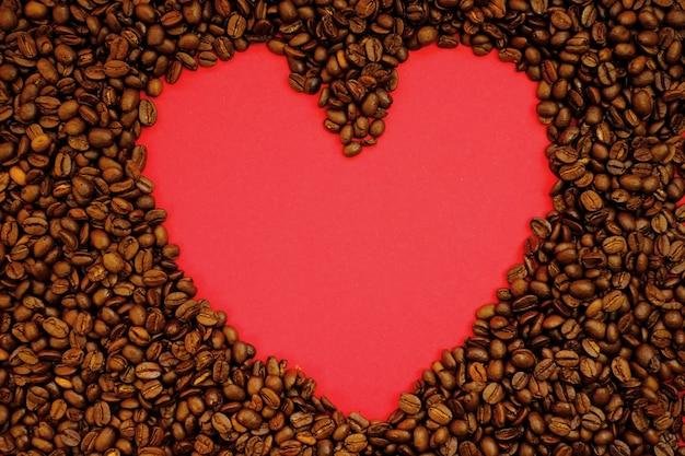 Макет кофе. жареные кофейные зерна и копия пространства в форме сердца на красном фоне. кофейный напиток