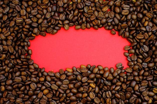 コーヒーのモックアップ。ローストしたコーヒーの粒と赤い背景のコピースペース。コーヒードリンク