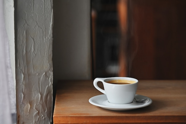 Coffee morning with black coffee on wooden desk.