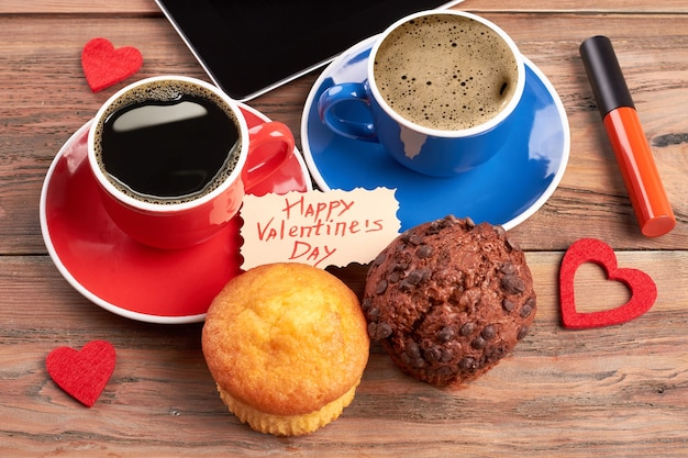 Coffee, muffins and greeting card. red lip gloss on wood. delicious present on valentine's day.