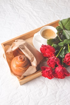 Coffee and muffins on a wooden tray. with a bouquet of flowers on the bed.