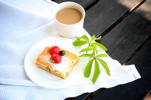 테이블에 커피 머그와 치즈 케이크입니다. 카푸치노와 달콤한 토피 케이크. 우유와 함께 라떼 또는 에스프레소