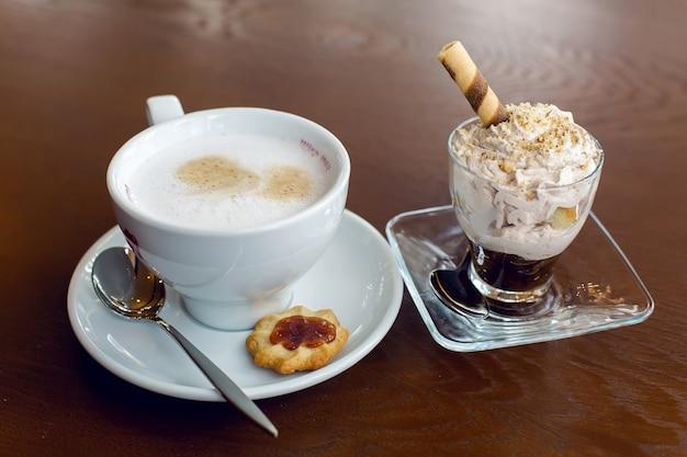 木製の茶色のテーブルの上に立っているコーヒーマグカップとデザート