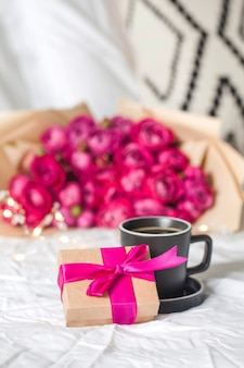 Coffee mug in bed on the surface of a bouquet of flowers and a gift