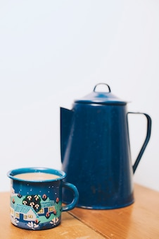 Coffee mug and blur teapot on wooden table against white backdrop