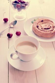Coffee in a mug, cupcake with cinnamon cherries on white