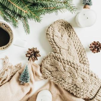 コーヒーマグ、モミの枝、ニットミトン、ベージュの毛布、装飾品。クリスマス休暇の構成。フラットレイ、上面図