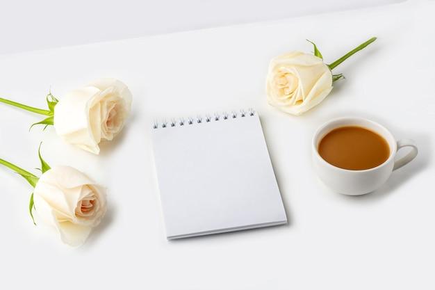 Кофейная кружка на завтрак, пустой блокнот. рабочее место женского блоггера.