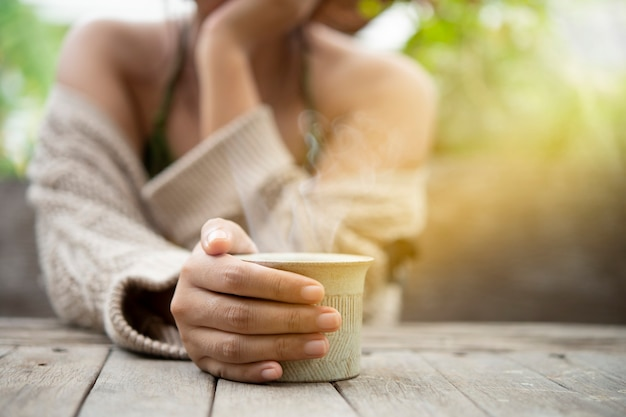 Кружка кофе в руке женщины на деревянном столе с космосом экземпляра. горячий кофе в осенней концепции.