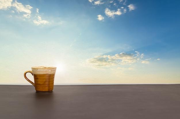 空と雲の景色を望むコーヒーマグがテーブルの上にあります