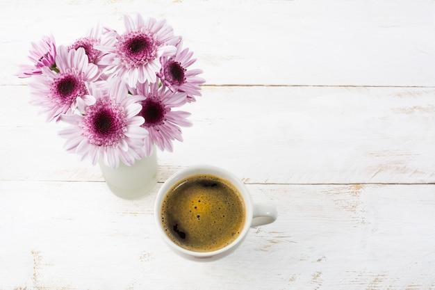 Coffee mug and lilac daisies, top view