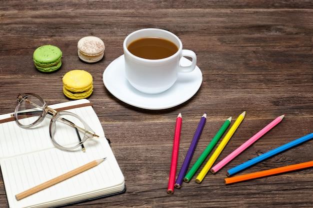Кофейная кружка, миндальное печенье, цветные карандаши и блокнот