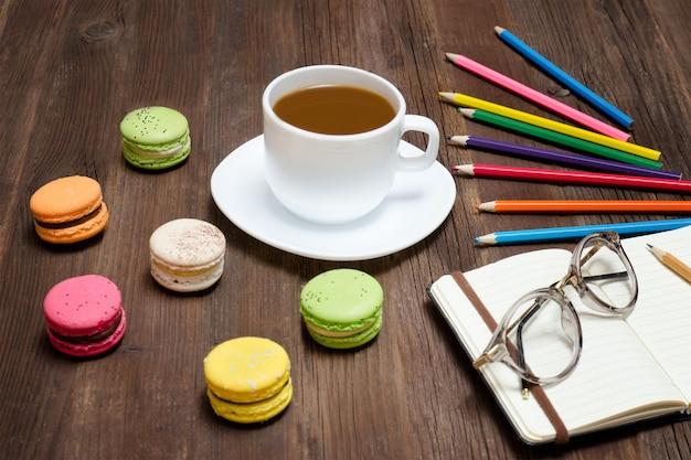 Кружка кофе, миндальное печенье, цветные карандаши и блокнот в очках на деревянном фоне
