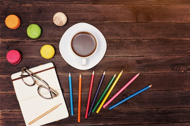 Кружка кофе, миндальное печенье, цветные карандаши и блокнот с бокалами на деревянном столе