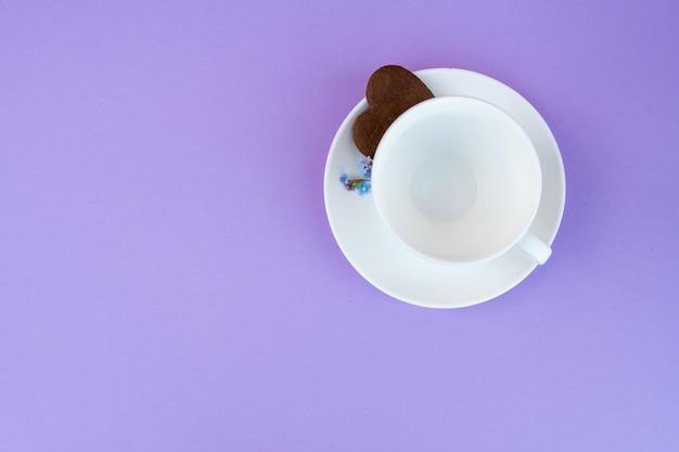 보라색 배경에 커피 잔입니다. 배경 아침 식사, 음료 및 카페 메뉴 개념-보라색 배경에 커피 컵 toplay flatlay. 커피 쿠키. 하얀 얼굴. 복사 공간