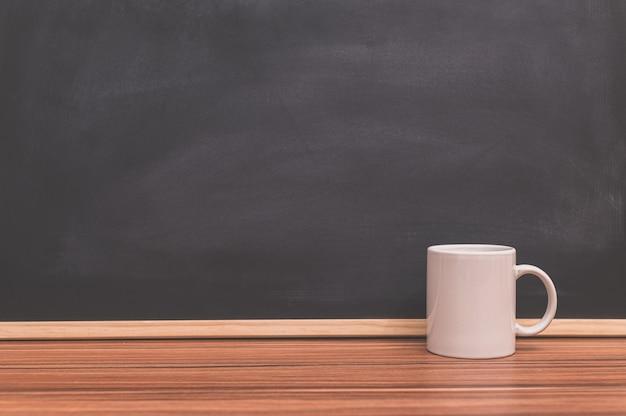 책상 칠판 배경에 커피 머그잔 마시는 사랑의 개념
