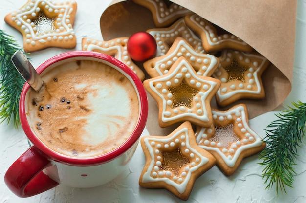 自家製のクリスマスの星の形の砂糖キャラメルクッキーと白いテーブルの上のコーヒーマグ